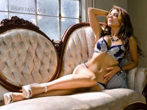 Kristy Jessica poses in lingerie on the couch.
